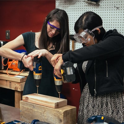 Students in a woodshop with safety equipment drilling on a piece of wood